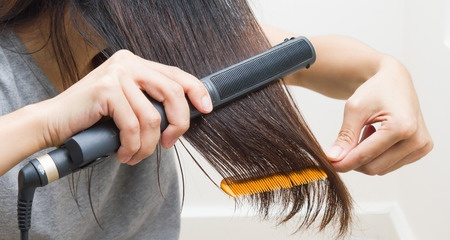woman straightening her hair